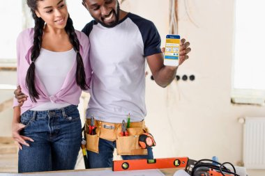 couple holding smartphone with booking website on screen during renovation