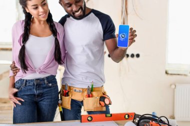 couple holding smartphone with shazam on screen during renovation