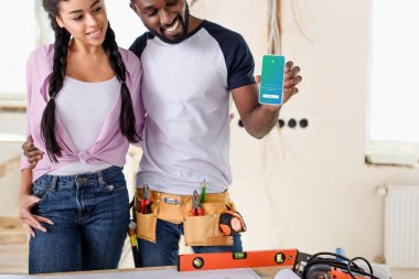 happy couple holding smartphone with twitter on screen during renovation at new home