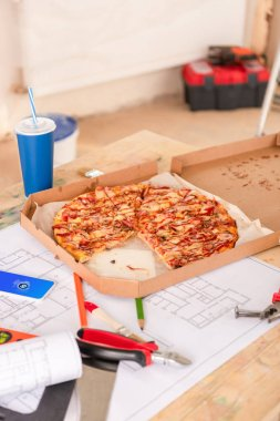 Selective focus of pizza, soda, blueprint, tools and smartphone with shazam on screen on table stock vector