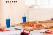 Selektivní fokus pizzu, soda, blueprint, nástrojů a smartphone s prázdnou obrazovkou na stole