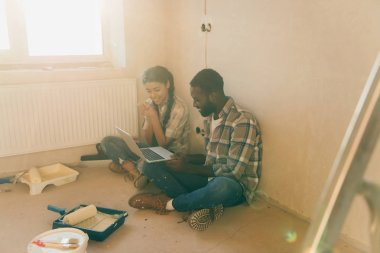 Smiling young african american couple resting with laptop during renovation of new home stock vector