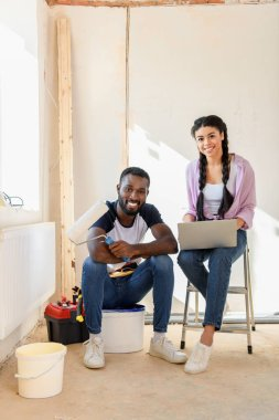 Smiling african american couple with laptop and paint roller looking at camera during renovation of home stock vector