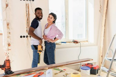 selective focus of happy african american couple posing during renovation of new home