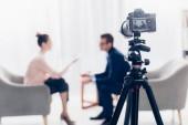 Fotografie podnikatel dává rozhovor novinář v úřadu, fotoaparát na stativu na popředí