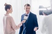 usměvavý pohledný podnikatel dát video rozhovor novinář v úřadu