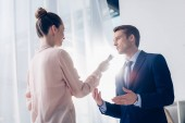 Photo low angle view of handsome businessman giving interview to journalist with voice recorder in office