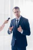 Photo cropped image of handsome businessman giving interview to journalist with voice recorder and looking at camera in office