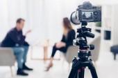 Fotografie podnikatelka v obleku dává rozhovor novinář v úřadu, fotoaparát na stativu na popředí