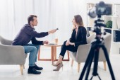 Photo side view of businesswoman in suit giving interview to journalist with voice recorder in office