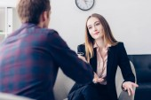 Photo selective focus of businesswoman in suit giving interview to journalist and gesturing in office