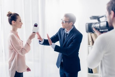 Handsome businessman in suit rejecting giving video interview to journalist and showing no gesture in office stock vector