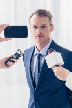 Handsome businessman giving interview to journalists and looking at camera in office stock vector