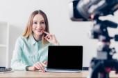 Fotografie usmívající se atraktivní ženské nezávislý záznam vlog v úřadu, notebook s prázdnou obrazovkou na desku stolu