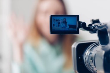 Selective focus of female video blogger recording vlog in office, camera on foreground stock vector