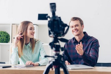 Selective focus of smiling video bloggers recording vlog in office stock vector