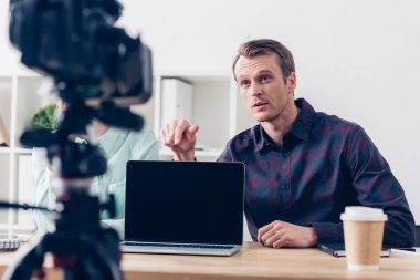 Video bloggers recording vlog and pointing on laptop with blank screen in office stock vector