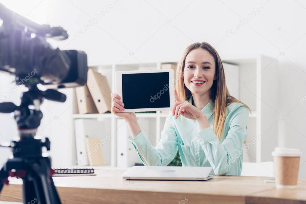 smiling attractive female video blogger recording vlog and showing tablet with blank screen in office