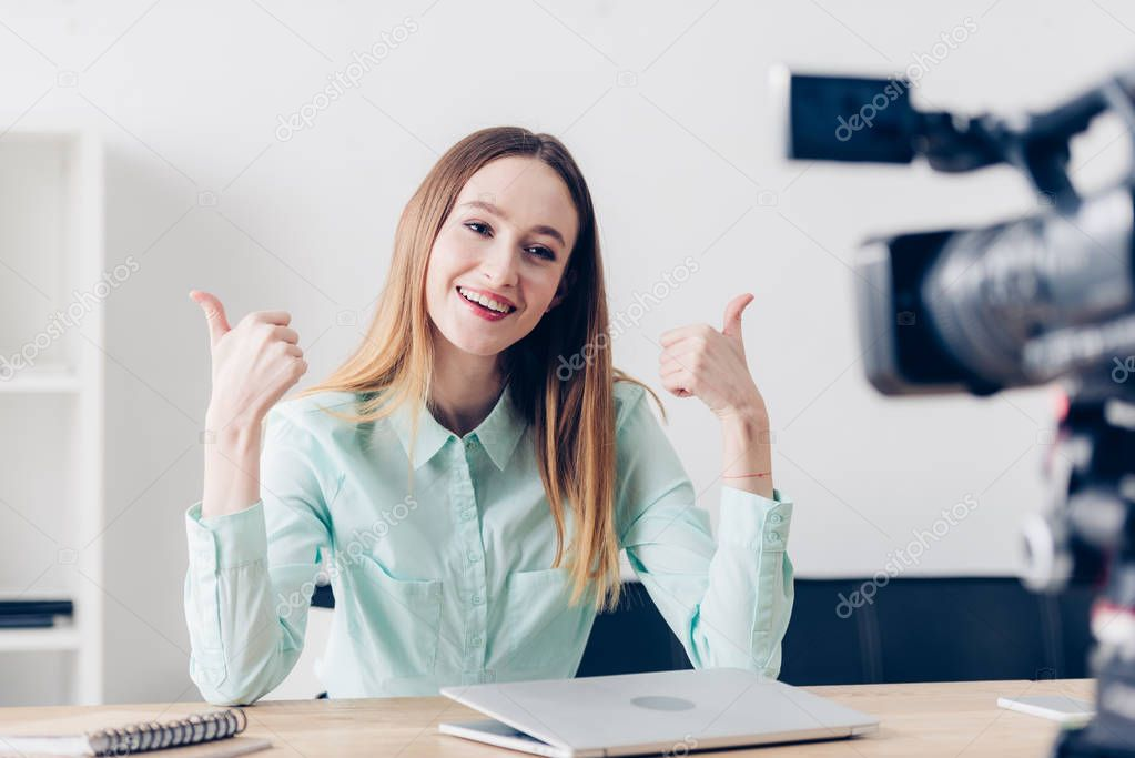Smiling attractive female video blogger recording vlog and showing thumbs up in office