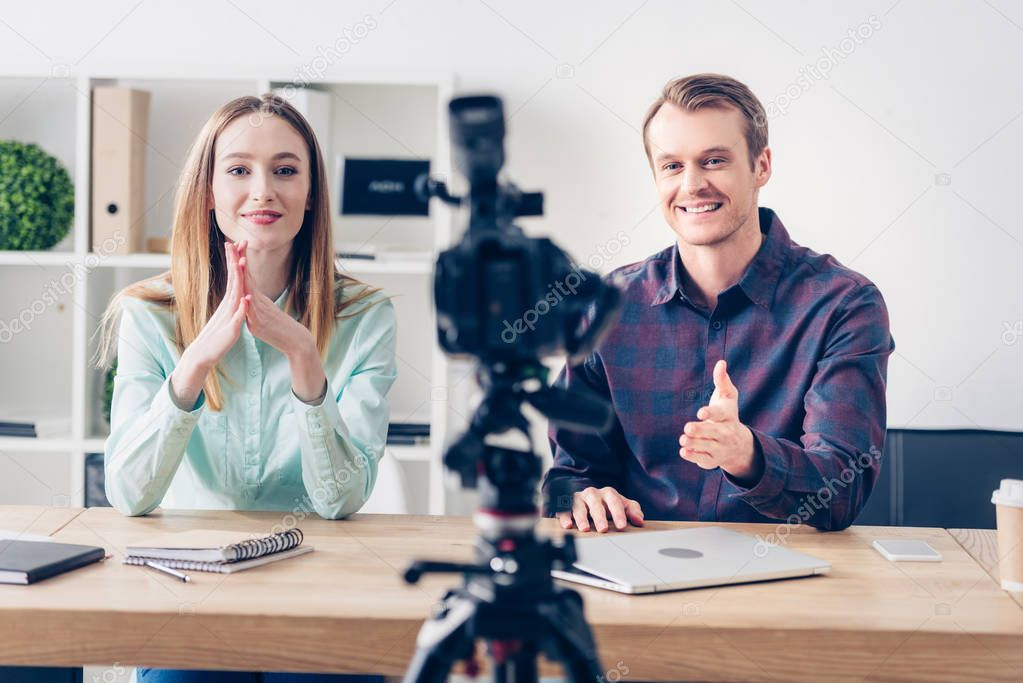 smiling video bloggers recording vlog in front of camera in office