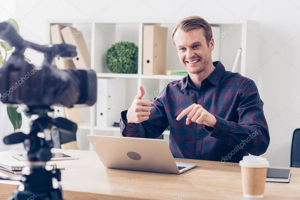 smiling handsome male video blogger recording vlog and showing thumb up in office
