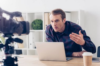 Aggressive male video blogger recording vlog and gesturing in office stock vector