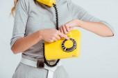 oříznutý pohled ženy vytáčení telefonního čísla na vintage žluté telefonní izolované Grey