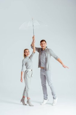 Excited couple standing on tiptoe and posing with transparent umbrella on grey background stock vector
