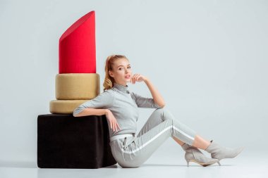 beautiful woman touching chin and posing near big red lipstick model on grey background