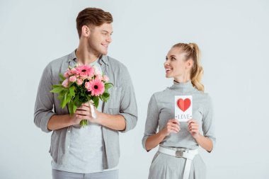 happy couple looking at each other and holding Valentines card and flower bouquet isolated on grey