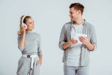 beautiful couple looking at each other and using digital tablet with headphones isolated on grey
