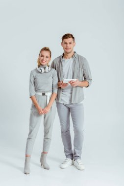 woman with headphones and man with digital tablet looking at camera on grey background