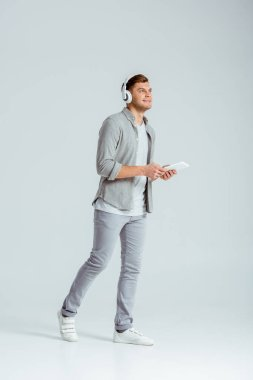 man wearing headphones, listening music and using digital tablet on grey background