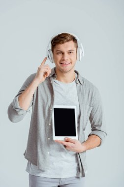 handsome man pointing with finger at headphones while holding digital tablet with blank screen isolated on grey