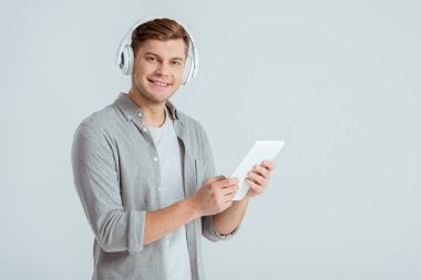 man in headphones listening music, looking at camera and using digital tablet isolated on grey