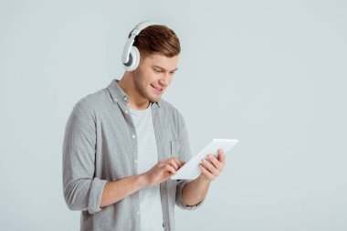 Handsome man in headphones listening music and using digital tablet isolated on grey stock vector