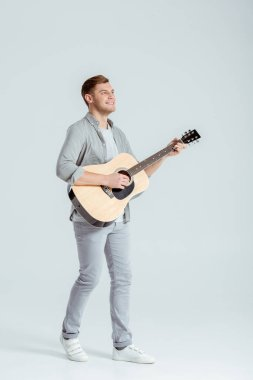 handsome man in grey clothing playing acoustic guitar on grey background