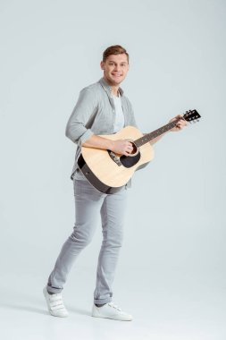 smiling man in grey clothing looking at camera and playing acoustic guitar on grey background