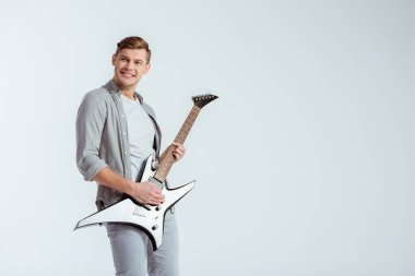 excited handsome man in grey clothing playing electric guitar isolated on grey