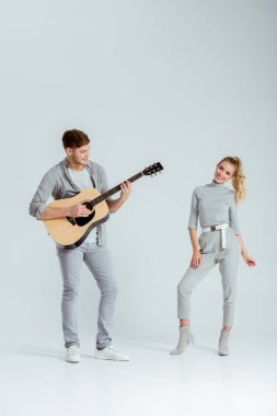 man playing acoustic guitar while smiling woman dancing on grey background