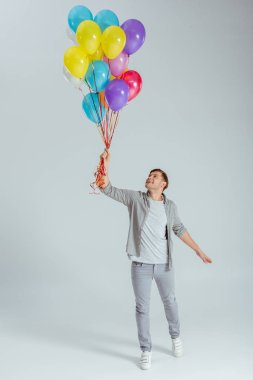 happy man in grey clothing holding bundle of colorful balloons on grey background