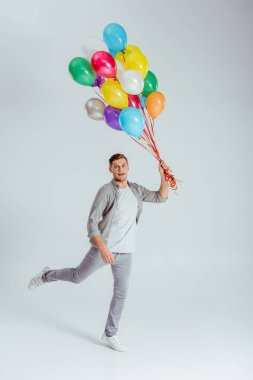 Man jumping with bundle of colorful balloons and looking at camera on grey background stock vector