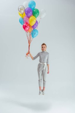 Beautiful smiling woman looking at camera and jumping in air with bundle of colorful balloons on grey background stock vector