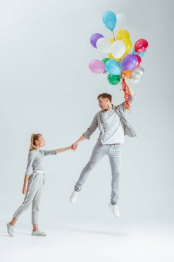 Beautiful woman holding hand of man jumping in air with bundle of colorful balloons on grey background stock vector