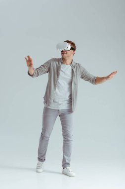 surprised man gesturing while wearing virtual reality headset on grey background