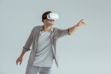 man in grey clothing gesturing while wearing virtual reality headset isolated on grey
