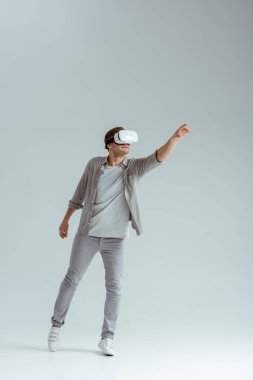 man in grey clothing gesturing while wearing virtual reality headset on grey background