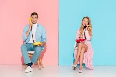 smiling couple sitting and having conversation on vintage telephones with pink and blue background