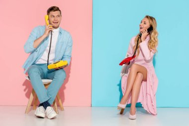 happy couple sitting and having conversation on vintage telephones with pink and blue background