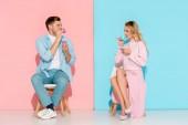 krásný pár sedí na židlích, při pohledu na sebe a pití kávy na růžové a modré pozadí